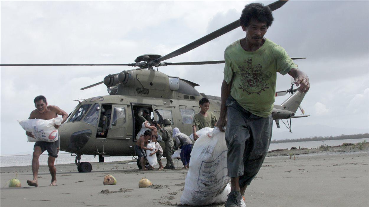 Des Philippins reçoivent des sacs d'aide alimentaire par des vols de l'armée.
