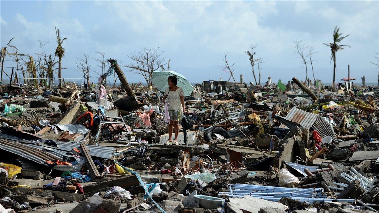 Une femme marche dans un champ de débris.