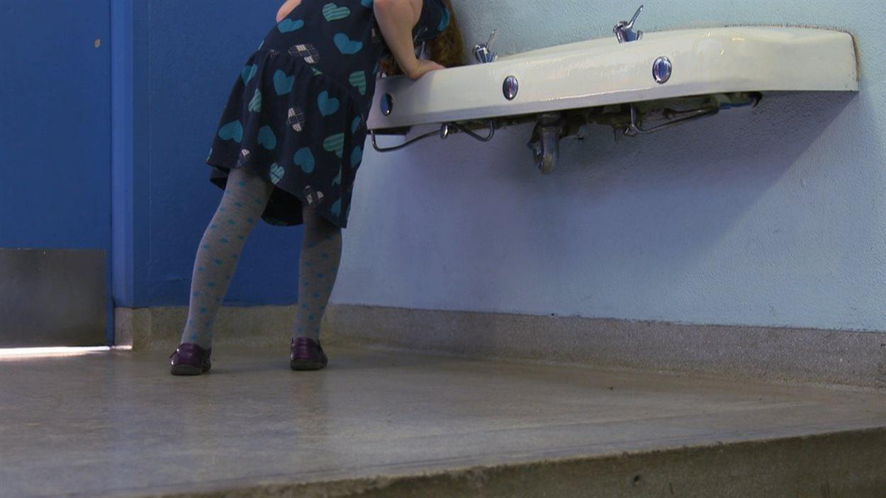 Une fillette boit de l'eau à une fontaine