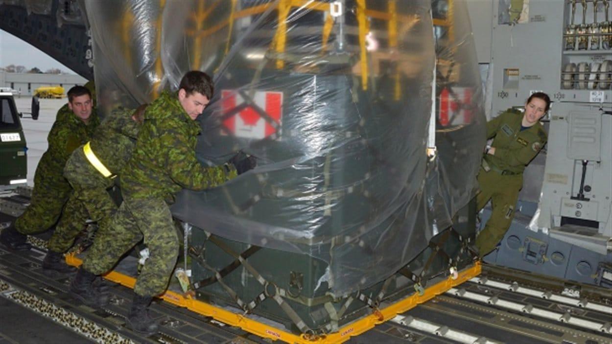 Des militaires canadiens chargent de l'équipement dans un avion  C177 Globemaster à Trenton, lundi, afin de se rendre aux Philippines.