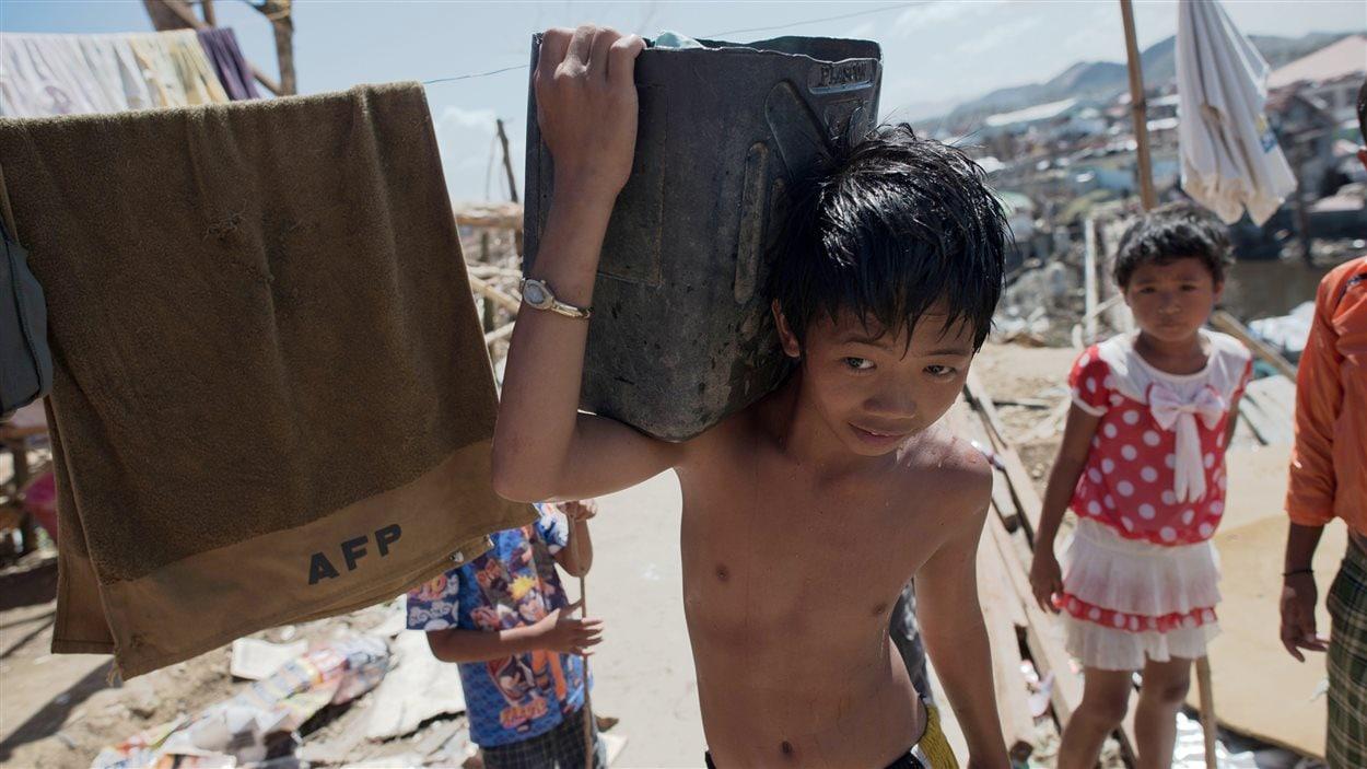 Un enfant philippin ayant survécu au passage du typhon Haiyan transporte de l'eau.