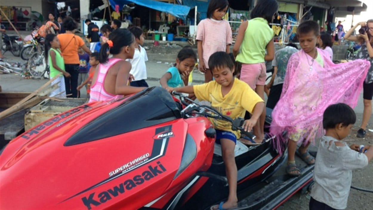 Des enfants jouent avec une motomarine apportée là par la vague.