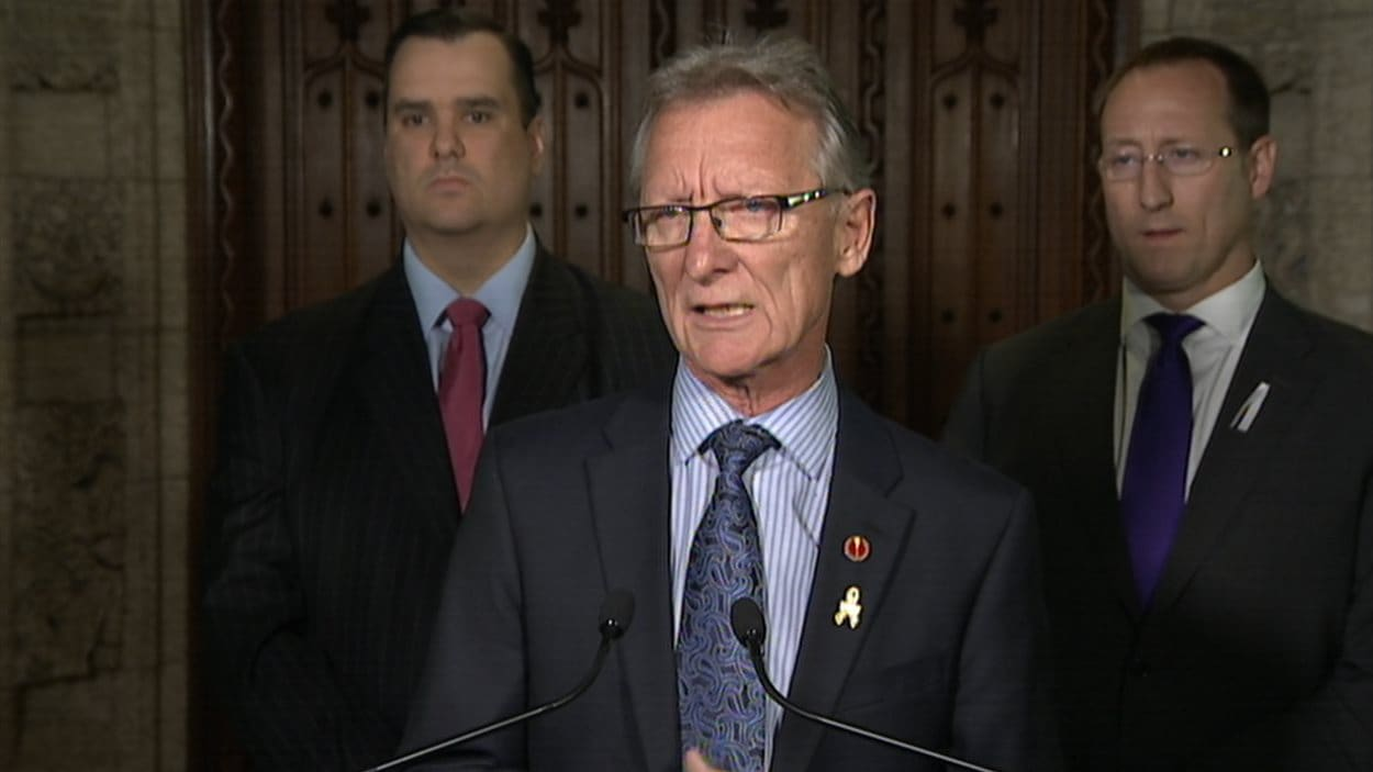 Le sénateur conservateur Pierre-Hugues Boisvenu. À l'arrière, le ministre de l'Industrie, James Moore, et le ministre de la Justice et procureur général du Canada, Peter MacKay.