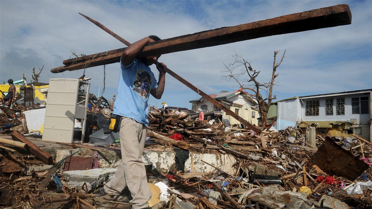 Un survivant transporte des débris à Tacloban.
