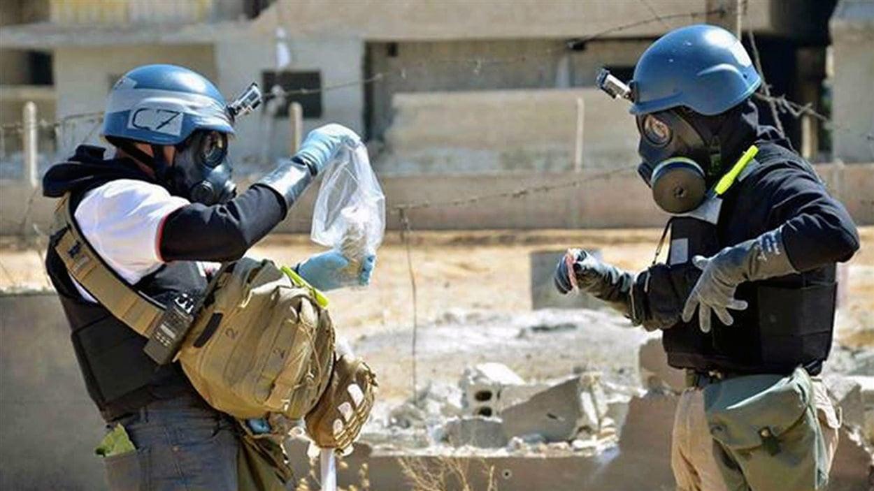 Des enquêteurs de l'ONU spcialisés en armes chimiques recueillent des échantillons en sol syrien.