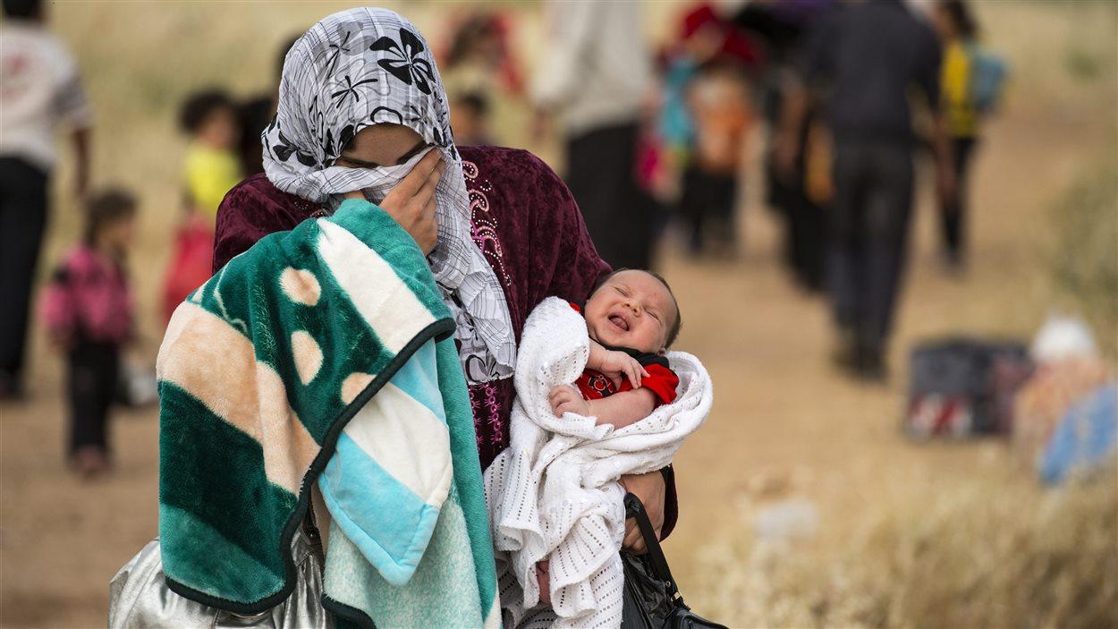 Une syrienne traverse la frontière jordanienne avec un jeune bébé.