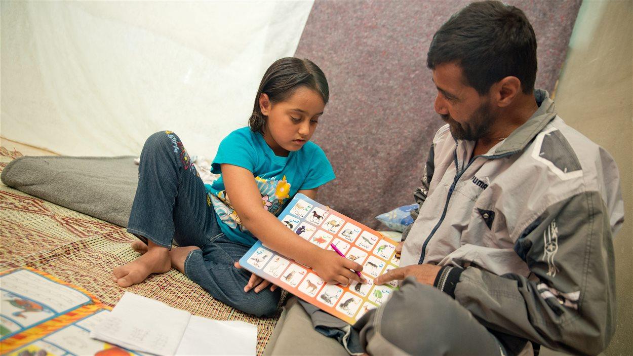 Un père syrien instruit sa fille dans un camp de réfugiés de Jordanie.