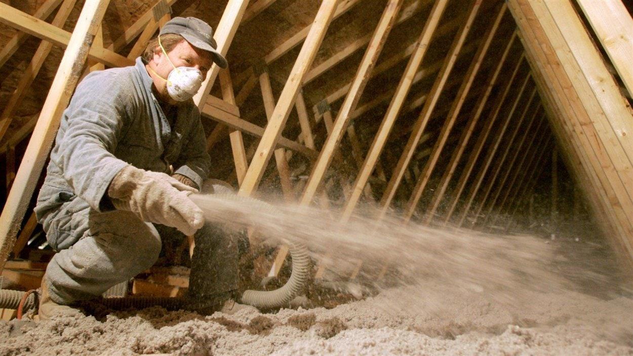 Un travailleur souffle de l'isolant dans le grenier d'une maison.