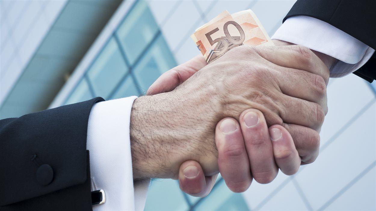 Deux hommes s'échangent une poignée de main... et 50 $.