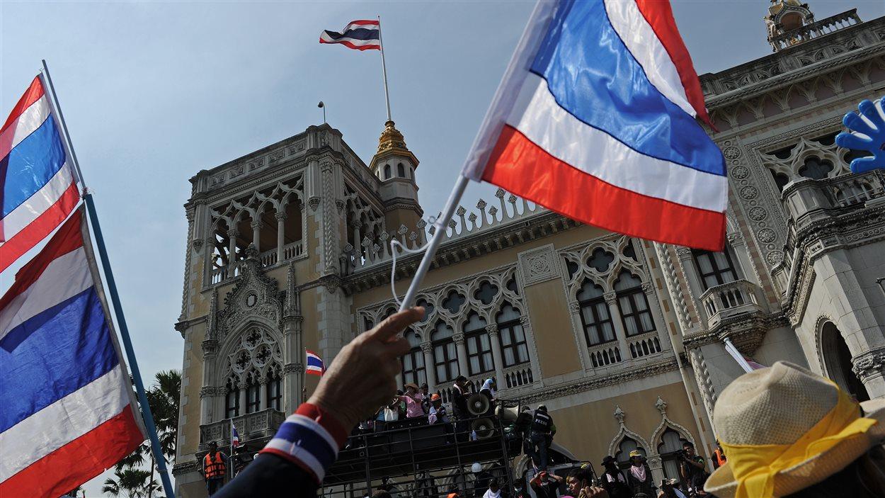 Un manifestant agite un drapeau de la Thaïlande devant le siège du gouvernement.