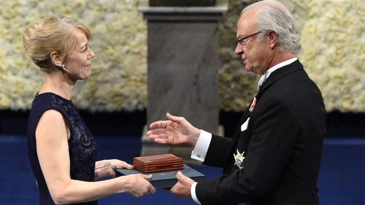 Jenny Munro, la fille d'Alice Munro, lauréate 2013 du prix Nobel de littérature, reçoit la médaille du prix, au nom de sa mère, des mains du roi Charles XVI Gustave de Suède, lors de la cérémonie officielle de remise de prix, le 10 décembre 2013 à Stockholm, en Suède.