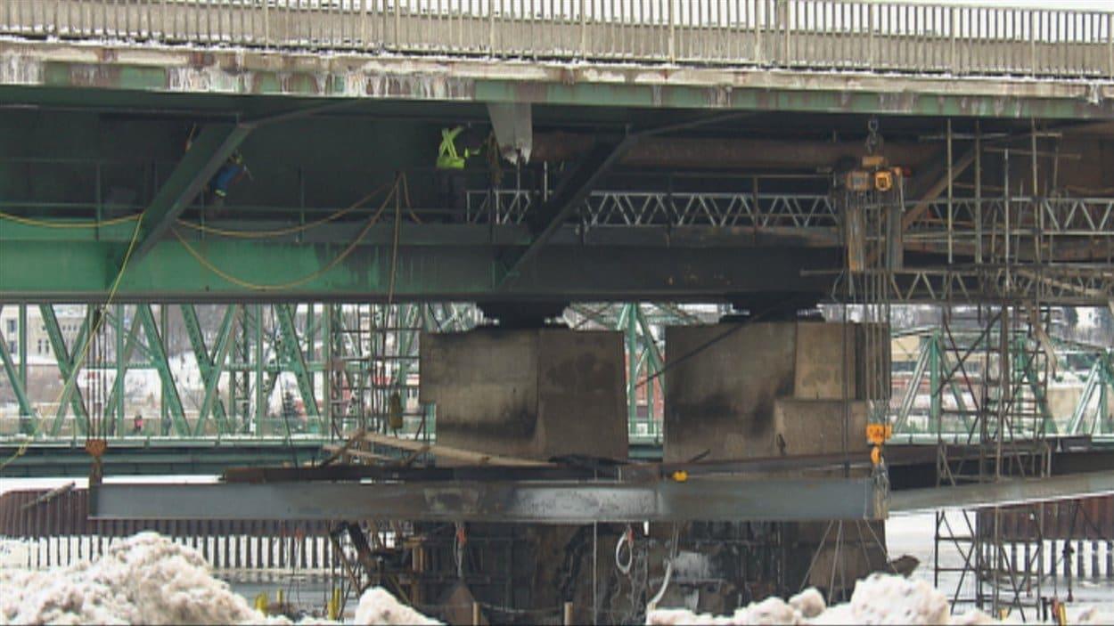 Plusieurs personnes s'affairent sous le pont Dubuc.