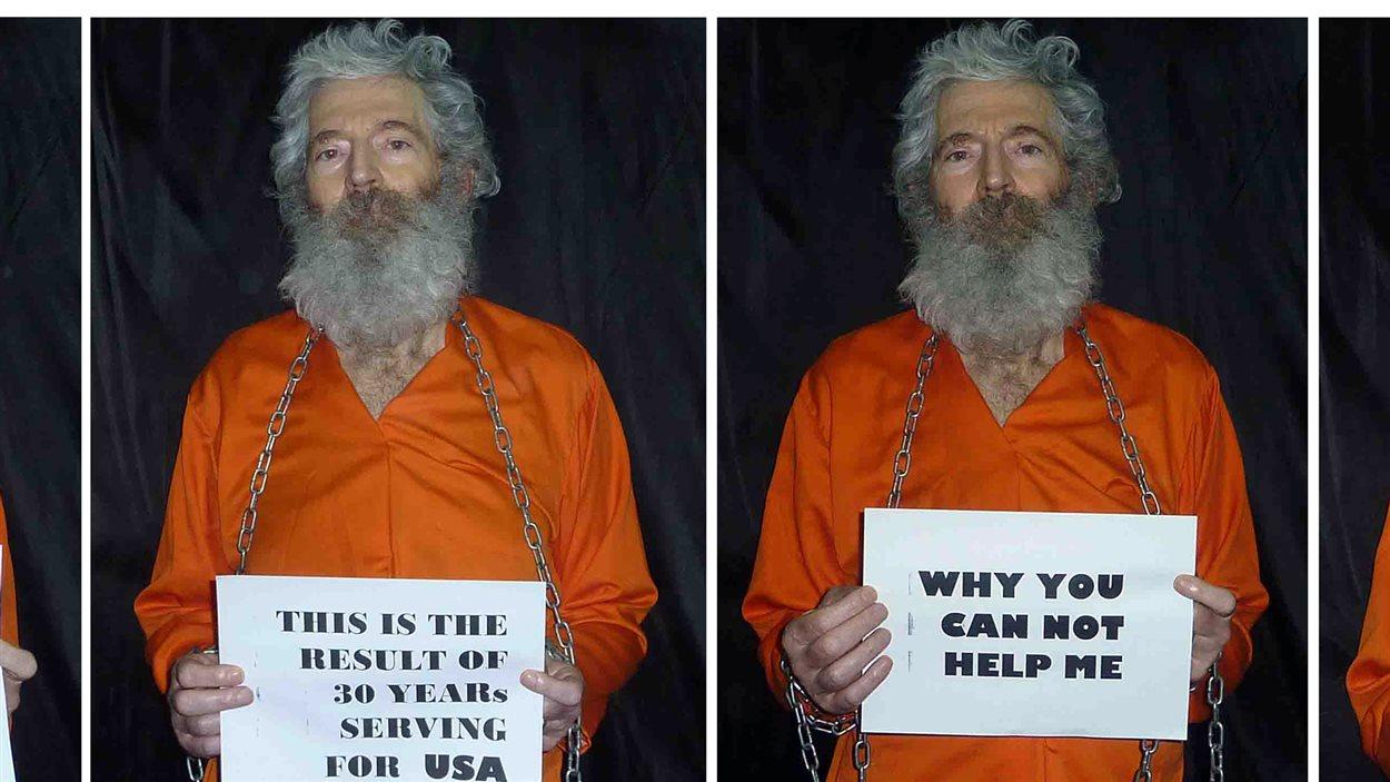 """Des photos reçues par la femme de Robert Levinson en 2011 le montrent en tenue orange, tenant une pancarte sur laquelle on peut lire: """"Pourquoi ne pouvez-vous m'aider?"""". On ignore où se trouve l'homme."""