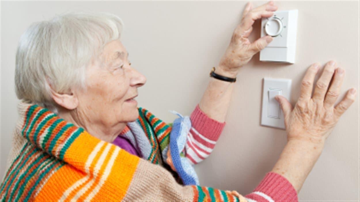 Une dame âgée ajuste le chauffage de sa maison