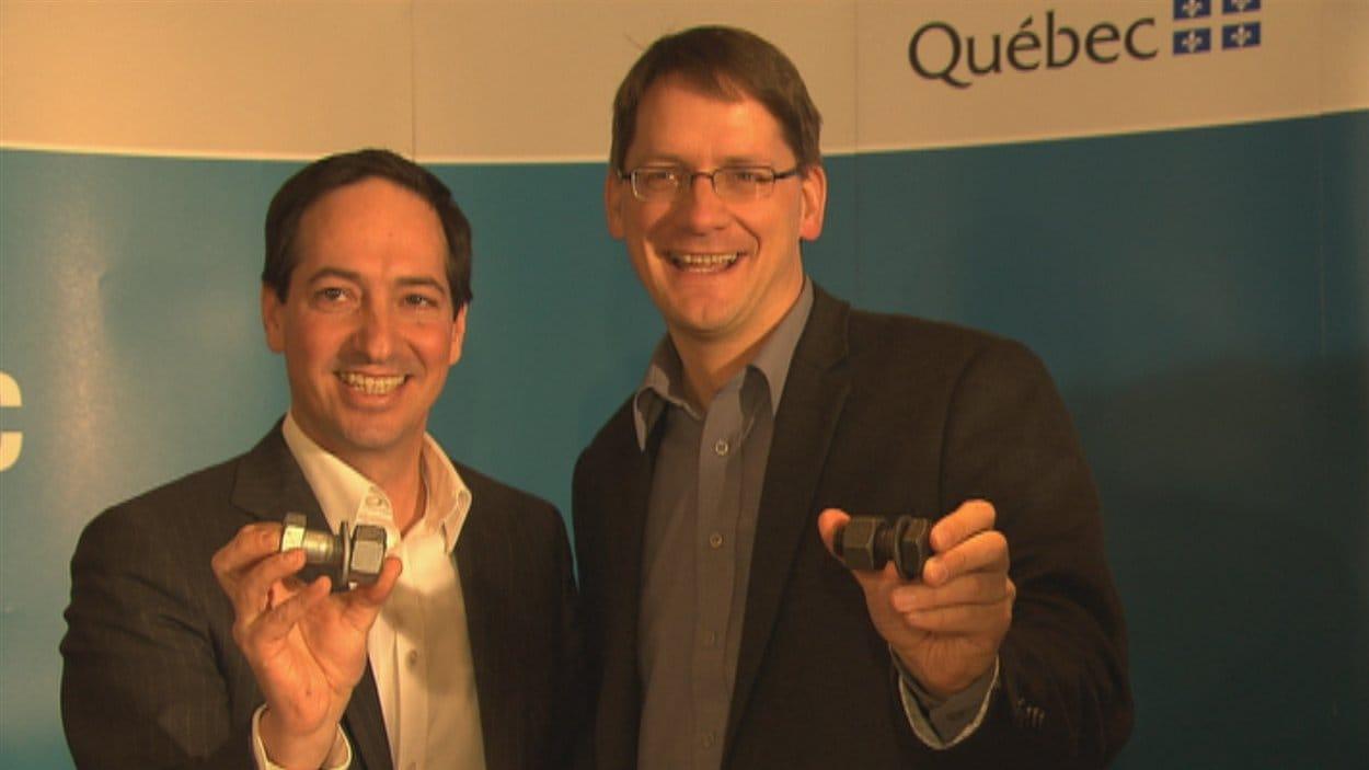 Stéphane Bédard et Sylvain Gaudreault montrent les boulons qui sont installés à l'intérieur de la structure du pont Dubuc.