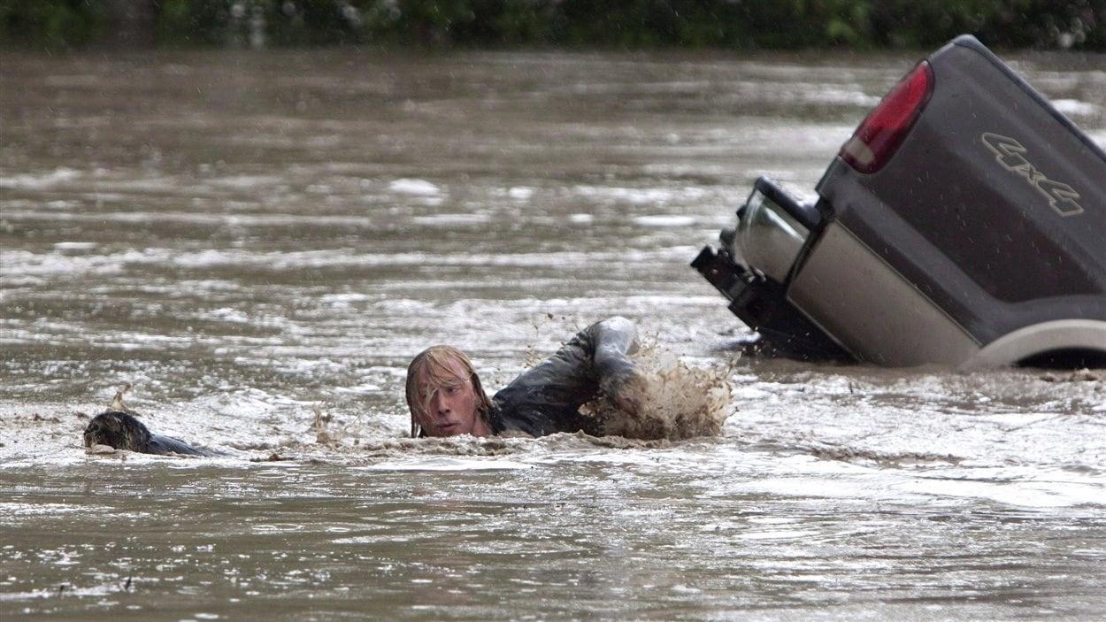 Un homme nage derrière son chat lors des inondations en Alberta.