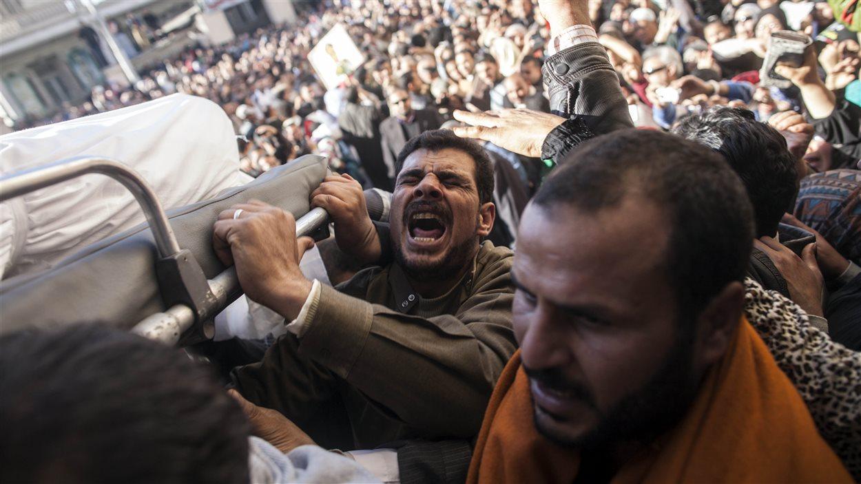 Des Égyptiens transportent le corps d'une des 13 personnes tuées dans l'attaque à la bombe à Mansura, en décembre 2013