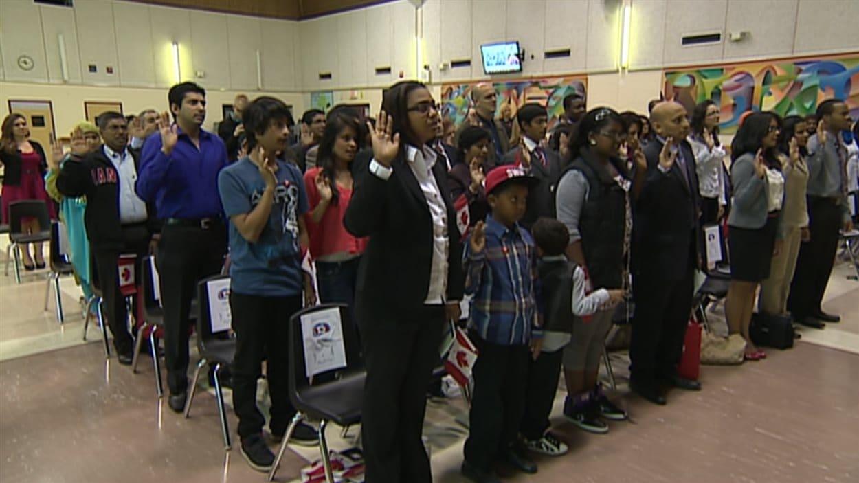 Des immigrants canadiens prêtent serment.