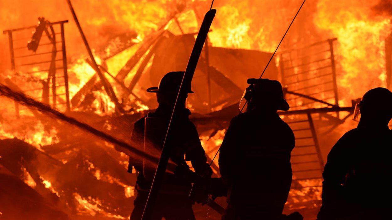 Des pompiers combattent les flammes.