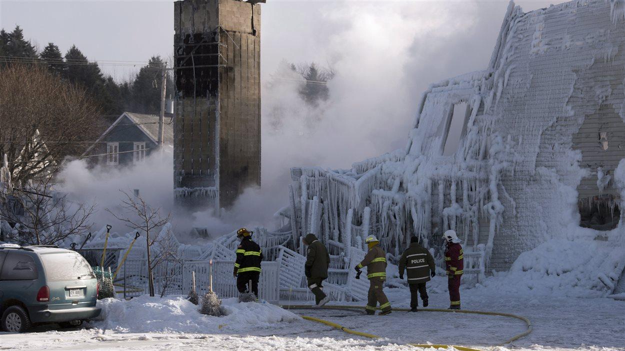 Des pompiers inspectent les décombres glacés de la résidence pour personnes âgées.