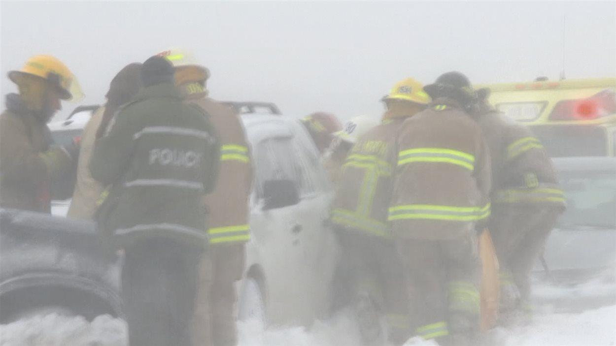 Des pompiers sortent des passagers de leur véhicule