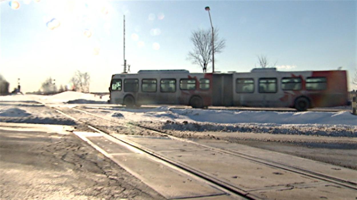 Un autobus d'OC Transpo, à Ottawa, approche d'un passage à niveau.