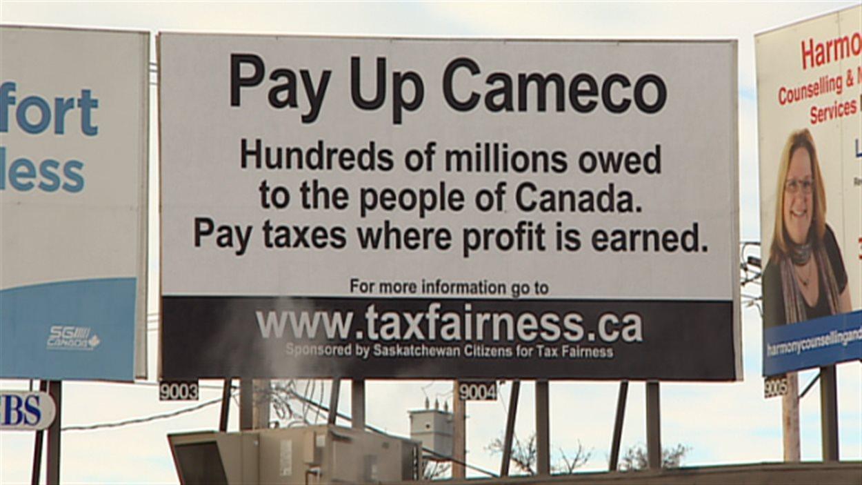 Un panneau publicitaire réclamant que l'entreprise Cameco paye ses impôts est filmé le 28 janvier 2014 à Saskatoon.