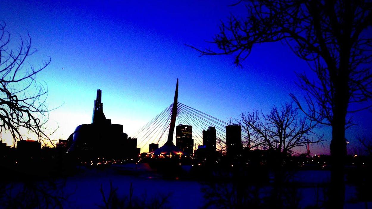 Le soleil se couche au loin, derrière le Musée canadien pour les droits de la personne, le pont Provencher et le centre-ville de Winnipeg le 28 janvier 2014.