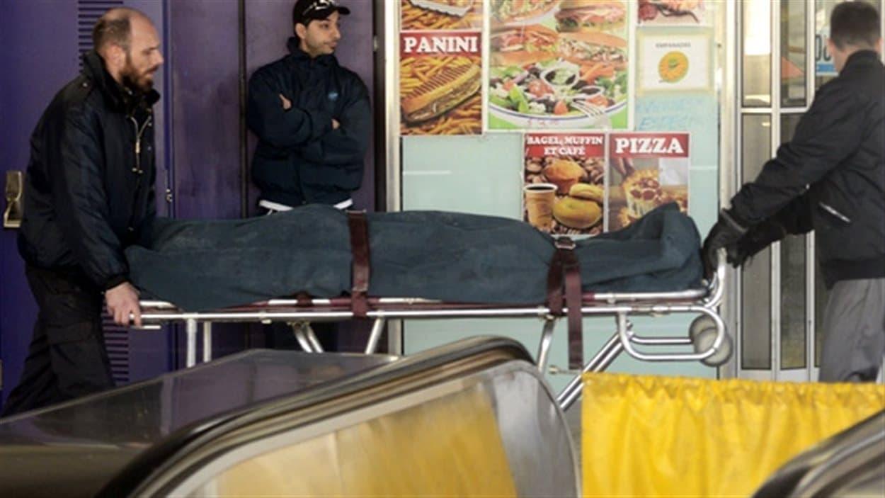 Des ambulanciers transportent un corps