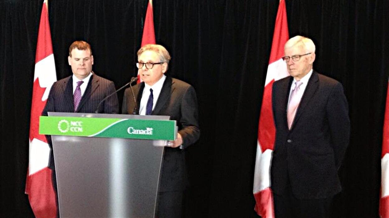 Le ministre responsable de la région de la capitale nationale, John Baird (à g.), a nommé Mark Kristmanson PDG de la CCN. À dr. le président de la CCN, Russell Mills.