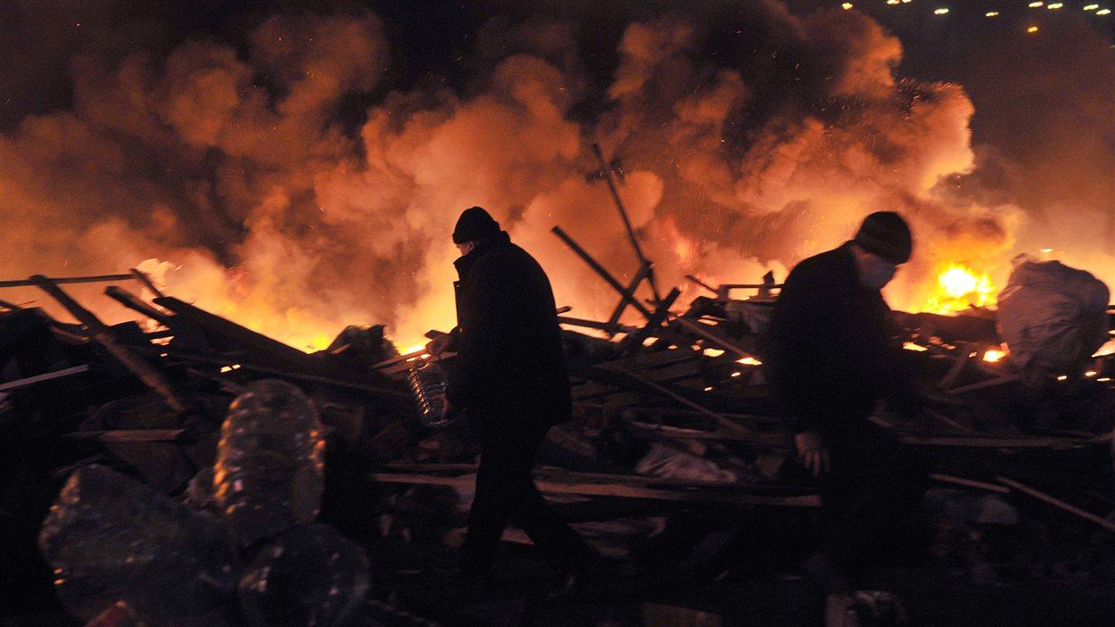 Cartons, panneaux de bois, tentes : un rideau de flammes a tenu provisoirement les policiers à distance.