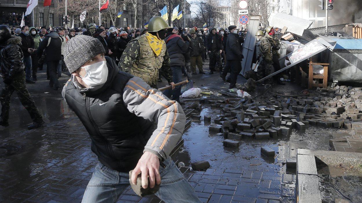 Des manifestants lancent des pavés à des policiers anti-émeute devant le parlement ukrainien