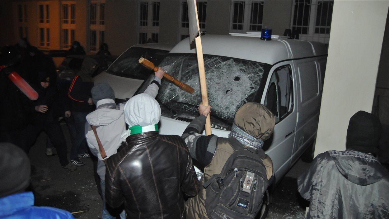 Des manifestants brisent la vitre d'une voiture de la police.