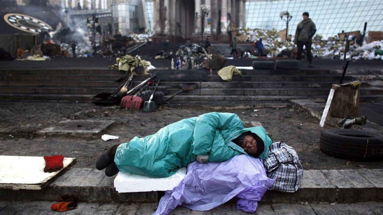 Un manifestant dort au milieu des décombres sur la place de l'Indépendance.
