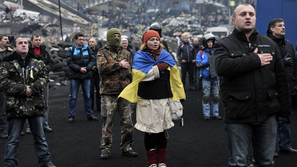 Des opposants au président ukrainien entonnent l'hymne national sur la place de l'Indépendance, épicentre de la contestation. Le président n'est plus à Kiev, et le gouvernement a ouvert la voie à une transition politique.