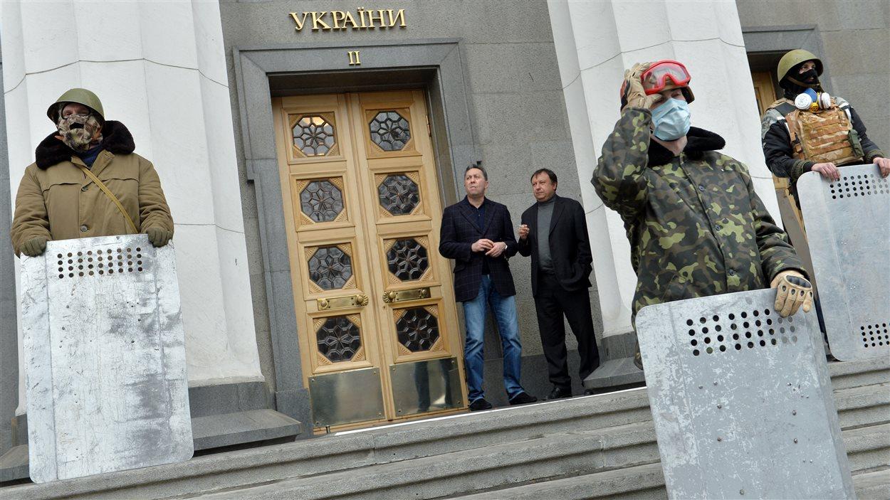 Des militants ukrainiens montent la garde devant le parlement, sous les yeux médusés des députés, samedi. Les principaux partis d'opposition ont demandé la démission de Viktor Ianoukovitch.