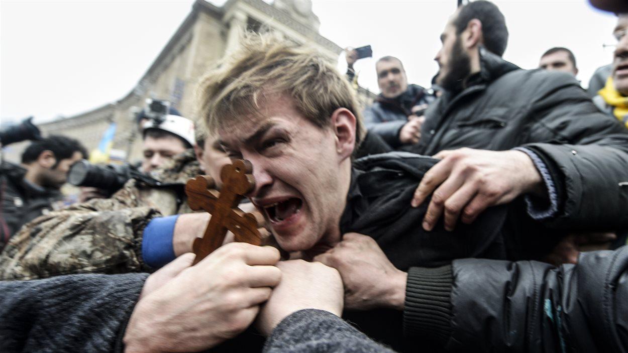 Une personne soupçonnée par des manifestants ukraniens d'être un tireur embusqué travaillant pour les services de sécurité est battue par la foule à Kiev.