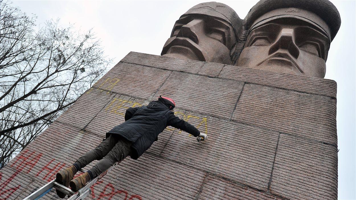 Un militant anti-gouvernemental vaporise un graffiti sur une statue soviétique à Kiev, le 23 février 2014