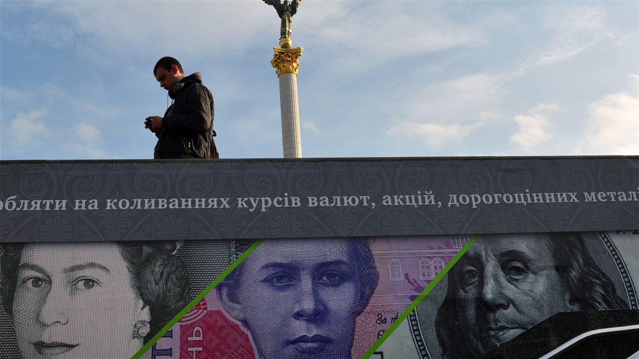 Un homme passe près d'une affiche publicitaire montrant des billets de banque britanniques, ukrainiens et américains, près de la place de l'indépendance, à Kiev (archives)