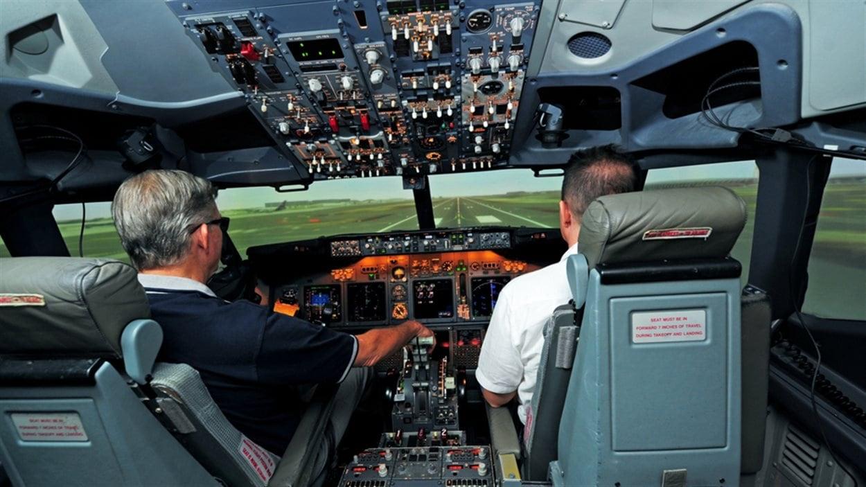 Un pilote en formation dans un simulateur de vol construit par CAE