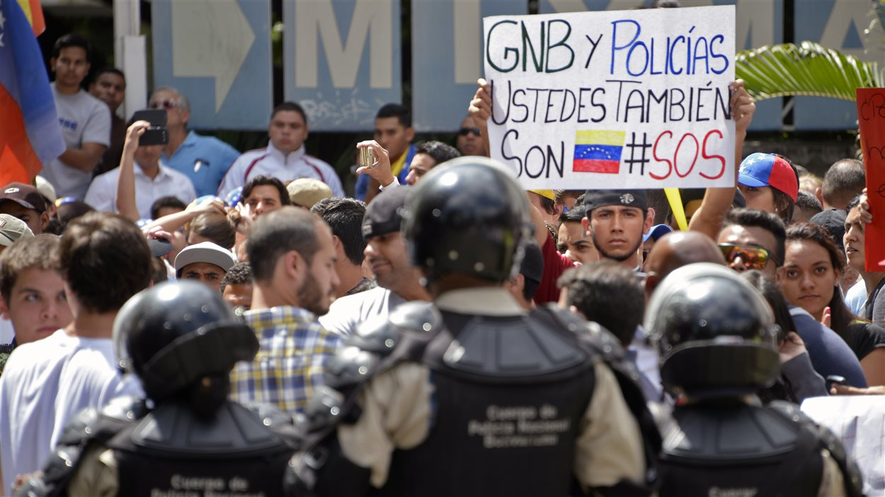 Un étudiant tient une pancarte disant «Garde nationale bolivarienne et policiers, vous êtes également Vénézuéliens SOS», lors d'une manifestation à Caracas le 17 février 2014.