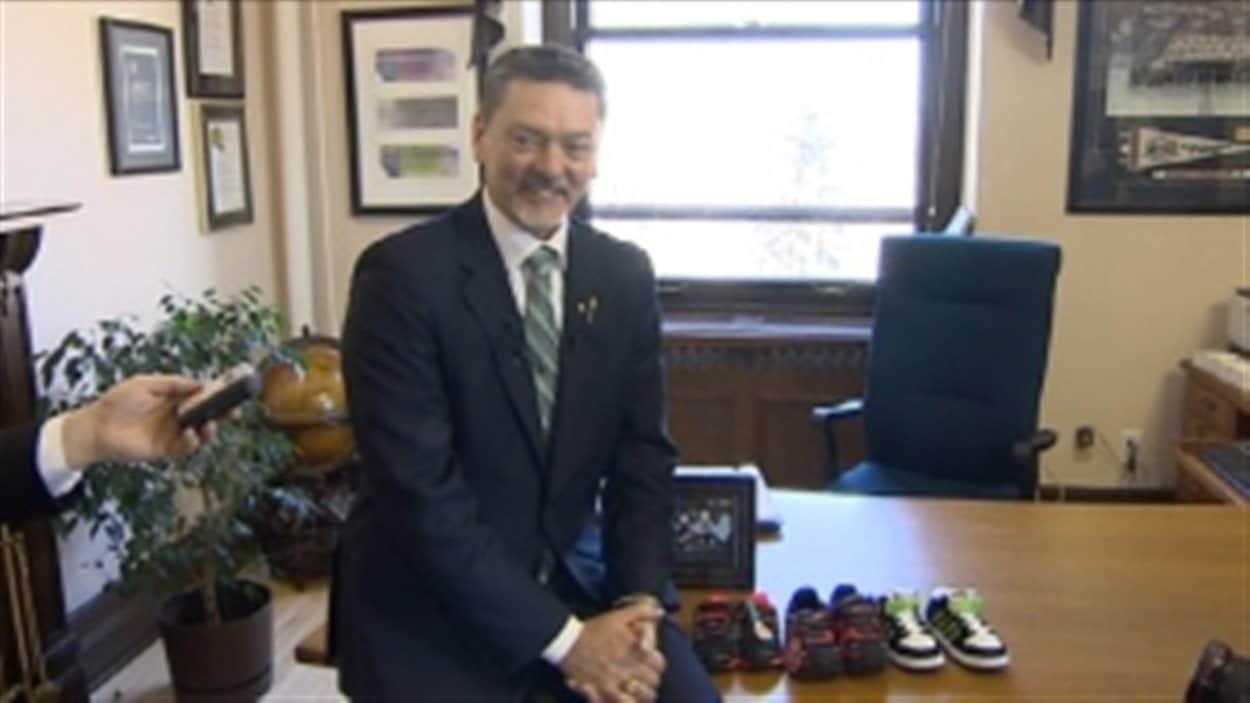 Le ministre des Finances Doug Horner avec les chaussures qu'il montre à la veille du dépôt de son budget 2014-2015