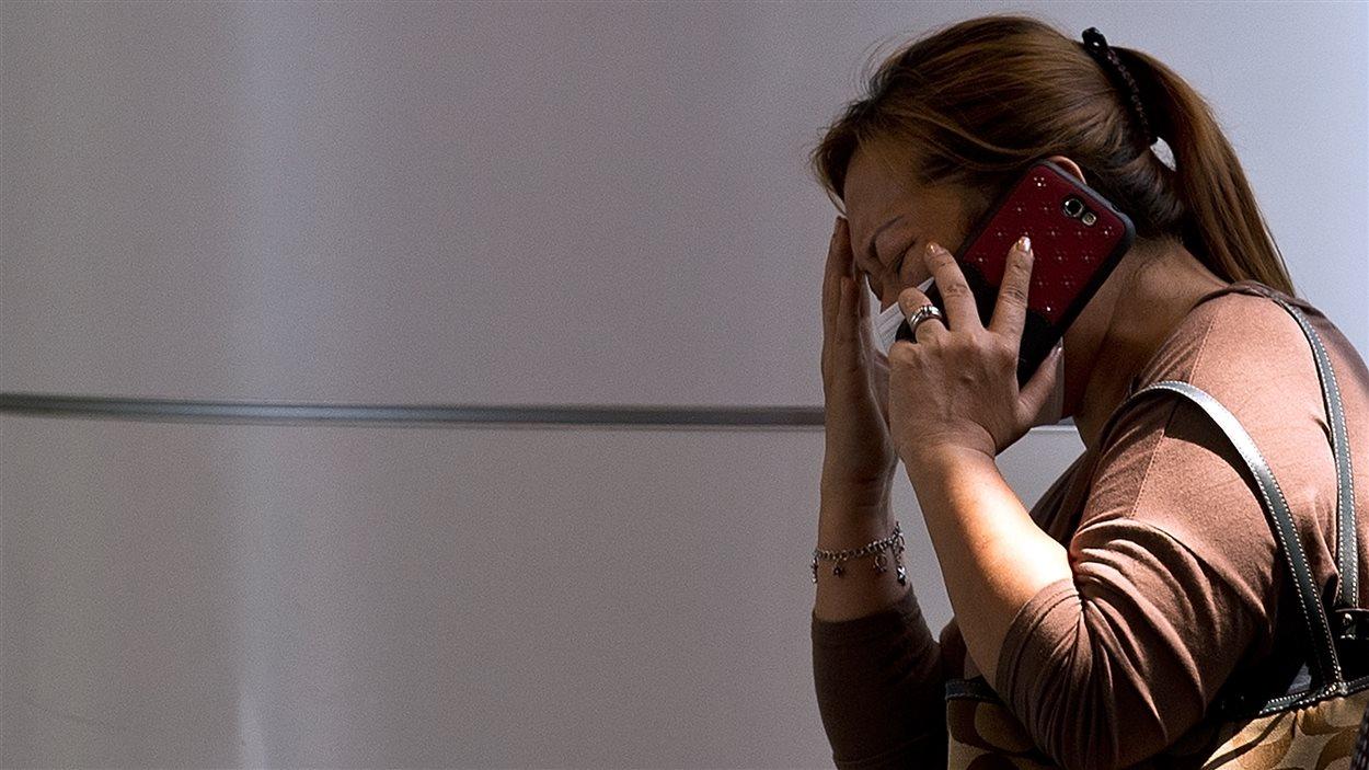 Une femme parle au téléphone dans le centre de crise organisé pour les proches des disparus à l'aéroport de Kuala Lumpur, le 8 mars 2014