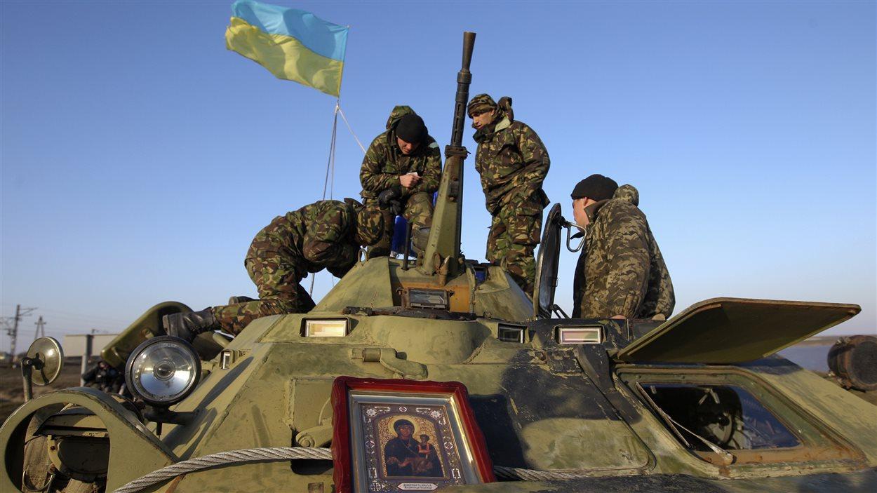 Des militaires ukrainiens s'activent sur un véhicule blindé près de la frontière de la Crimée.
