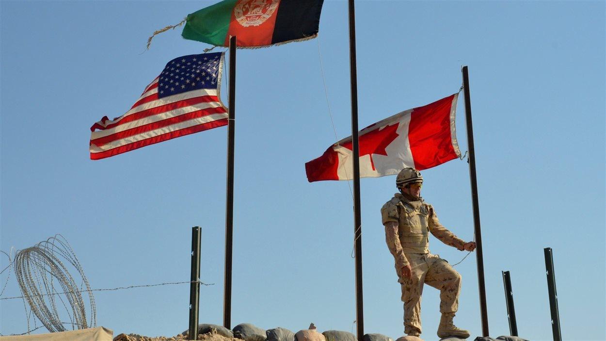 Pte. Danny Drapeau, of Alpha Company 1st Battalion Royal 22e Regiment, waits to lowers the Canadian flag for the last time at Forward Un soldat canadien s'apprête à mettre le drapeau canadien en berne à la base de Zangabad, en Aghanistan, lors du retrait des forces canadiennes de Kandahar (archives).