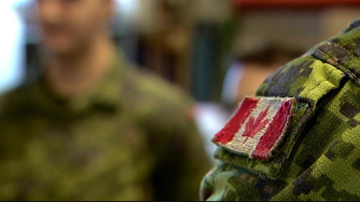 Un soldat porte l'uniforme avec le drapeau canadien sur l'épaulette, à la base d'Edmonton, le 6 mars 2014.