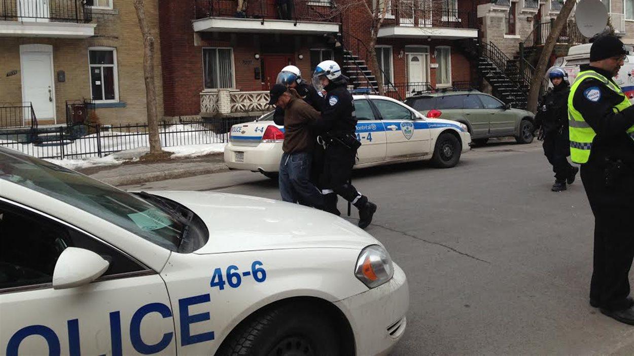Un homme est emmené par les policiers.