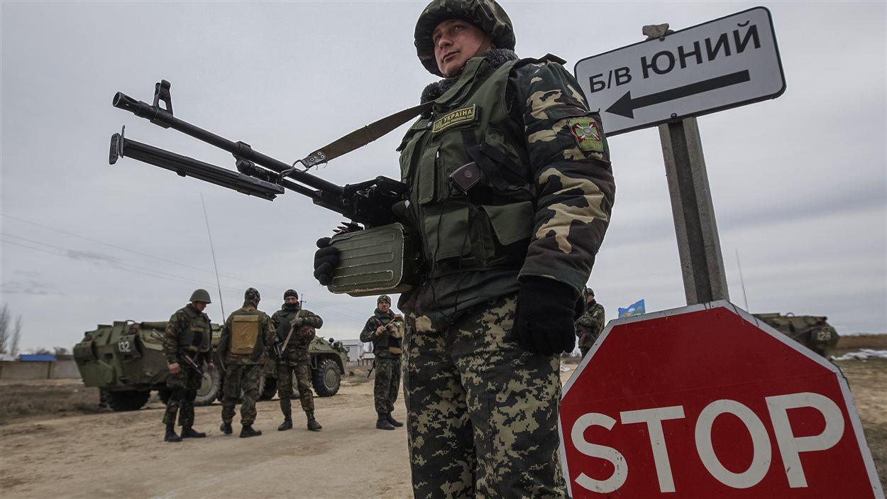 Un soldat urkrainien garde un poste de contrôle à la frontière de la Crimée, le 16 mars 2014.