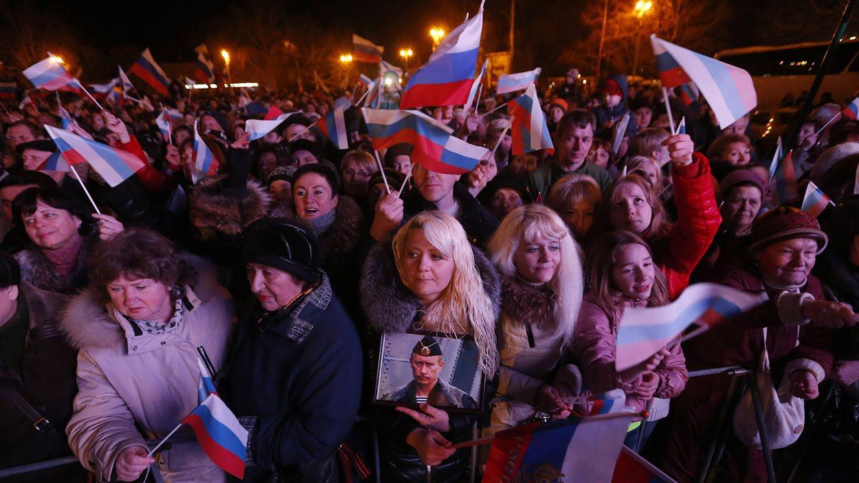 Une femme tient une photo de Vladimir Poutine en attendant les résultats du référendum sur l'avenir de la Crimée, le 16 mars 2014.