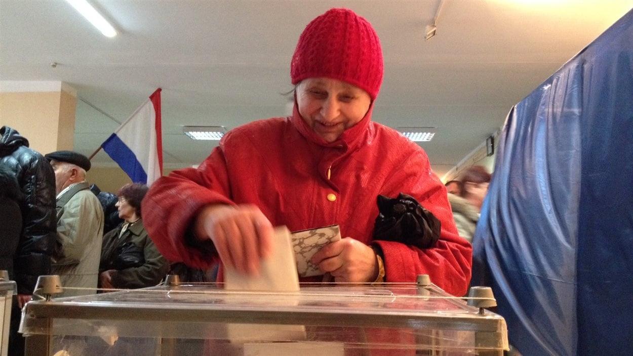 Une dame dépose son vote sur le rattachement de la Crimée à la Russie, le 16 mars 2014